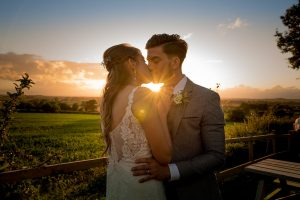 A bride and groom kissing on their wedding day at sunset in Sherborne Dorset