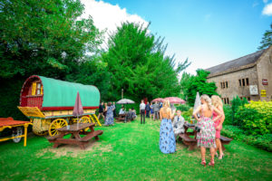 Wedding guests waiting in the garden for the ceremony to start at Haselbury Mill Riverside Restaurant