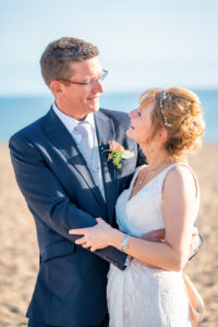 A bride and groom on their wedding day on West bay beach in Dorset.