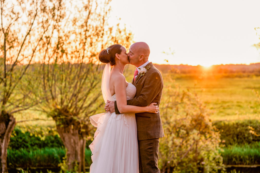 Bride and groom at sunset at The Almonry Barn Wedding Venue in Somerset