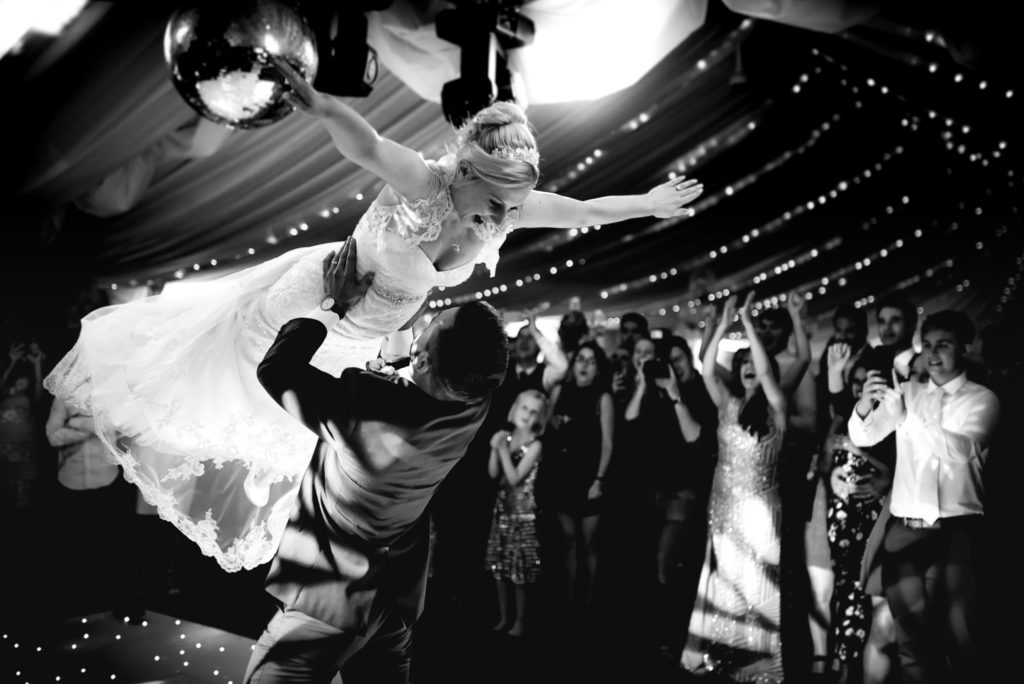 A bride and groom perform a dance move from flash dance where the groom holds the bride above his head.