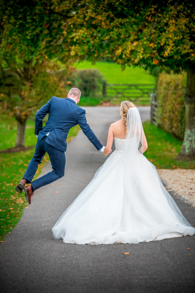 A groom leaps with joy whilst holding his bride's hand on their wedding day at Gate Street Barn in Surrey.