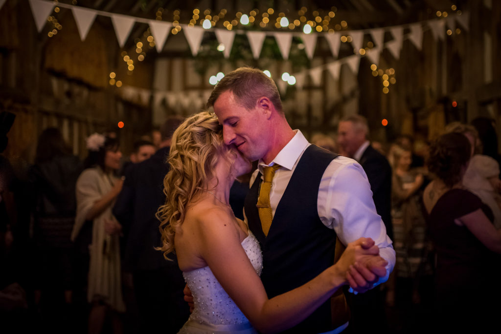 A bride and groom dance together on their wedding day in a barn with fairylights in the background.
