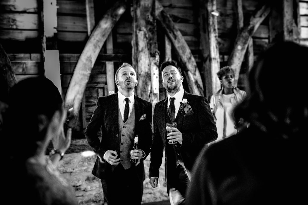 Two men sing and play the air guitar at a wedding in Stockbridge Farm in Sherborne Dorset