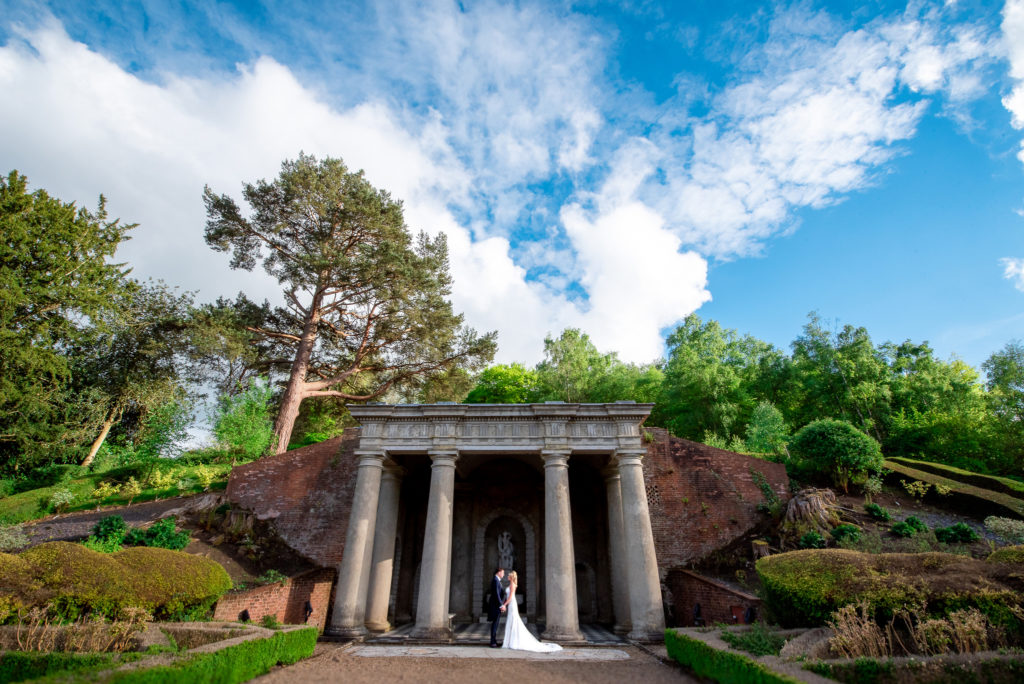 A bride and groom holding each other outside a folly monument at Wooton House in Hampshire.