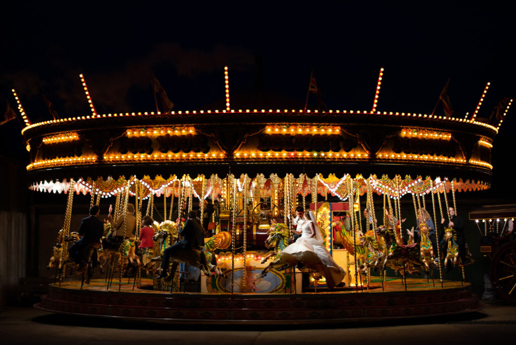 A bride and groom riding a classic steam driven carousel on their wedding day.