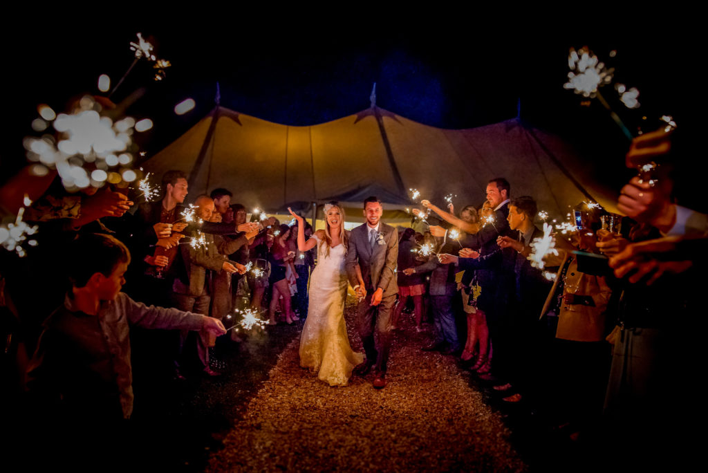 A bride and groom walking through a tunnel of sparklers held by their wedding guests.