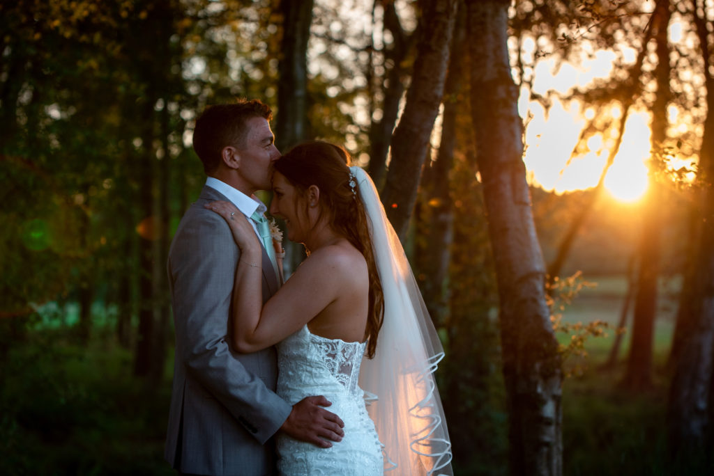A groom kissing a Bride's head in a forest at sunset on their wedding day.