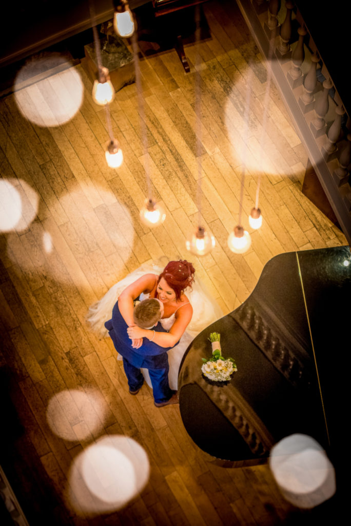 A bride and groom chat by a piano at the bottom of the stairs at Balmer Lawn Hotel on their wedding day.