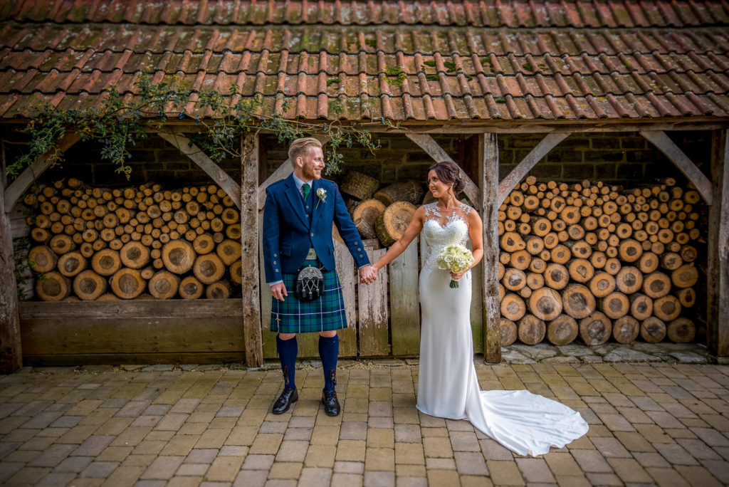 A bride and groom by the log store at The Almonry Barn, Muchelney in Somerset. The groom is wearing a kilt.