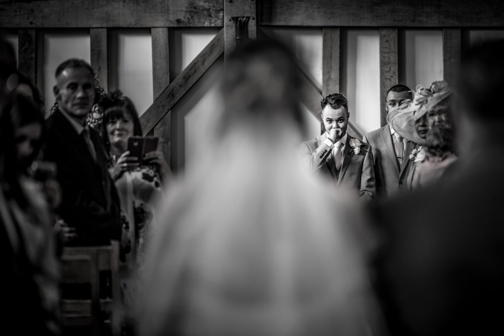 A groom looking emotional while his bride walks down the isle toward him at Gate Street Barn in Surrey.