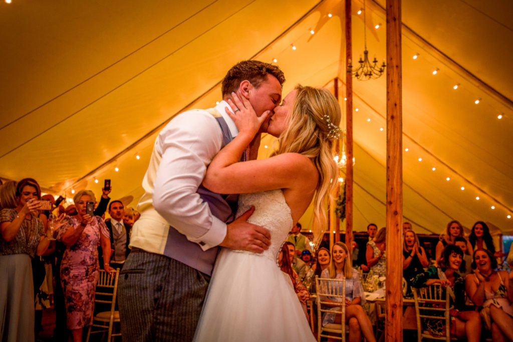 Bride and Groom embracing and kissing during their first dance inside the marquee at Old Oak Farm Wedding Venue in Curry Rival in Somerset