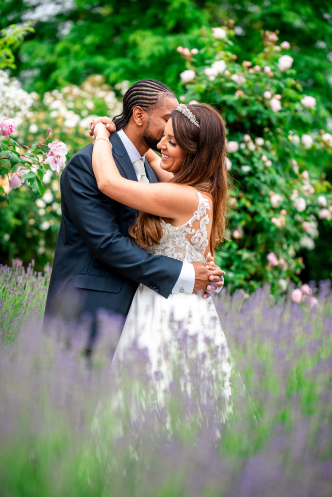 A newly married bride and groom hug whilst surrounded by roses and heather.