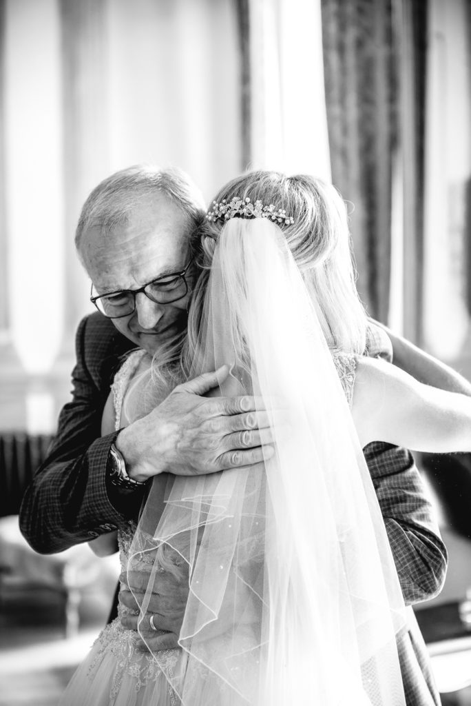 A bride hugs her father as they get emotional on her wedding day prior to the ceremony.