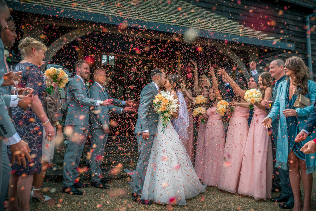 real petal Confetti being thrown at a newly married bride and groom.
