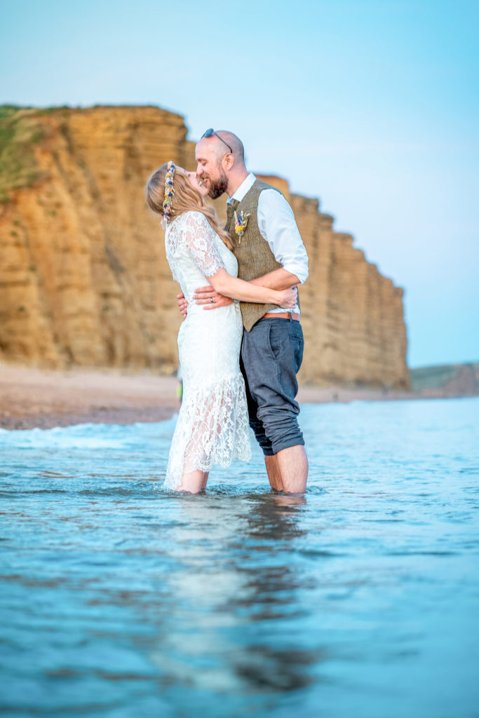 A stylish couple kissing whilst stood in the sea at West Bay in Dorset with the cliffs in the background.