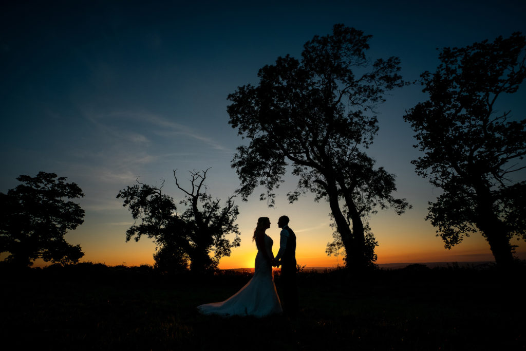 Silhouette of a bride and groom at sunset at The Wind whistle near Chard in Somerset.