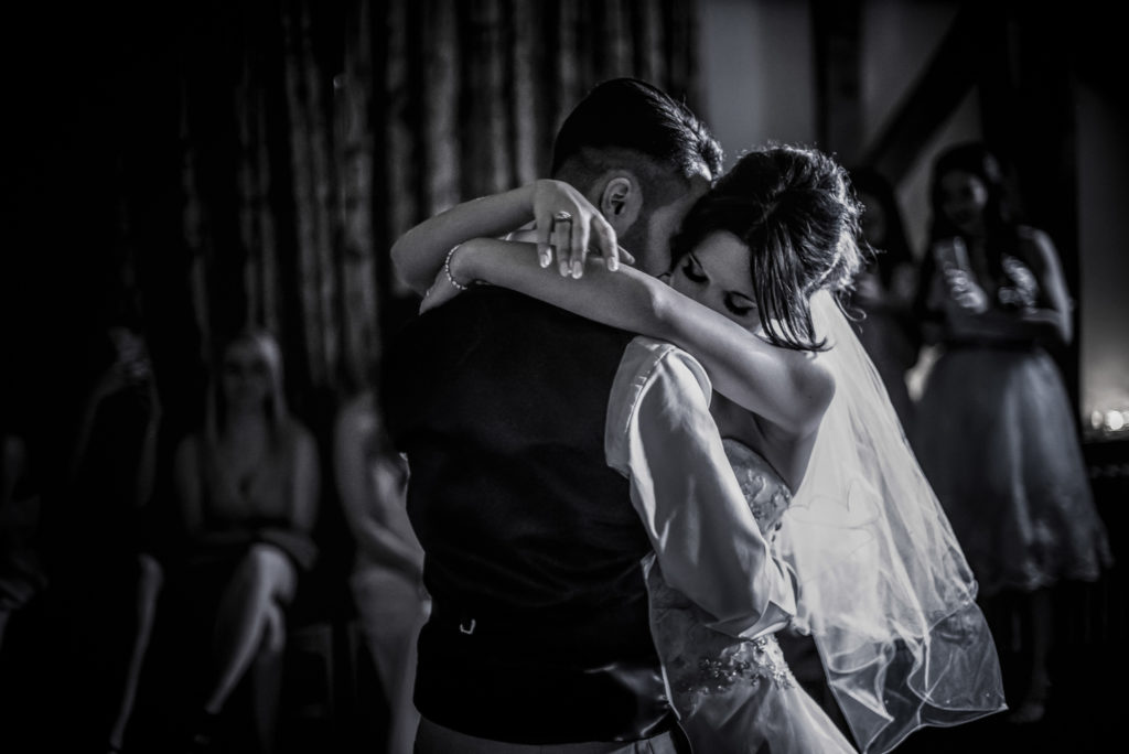 black and white image of a bride and groom hugging during their first dance.