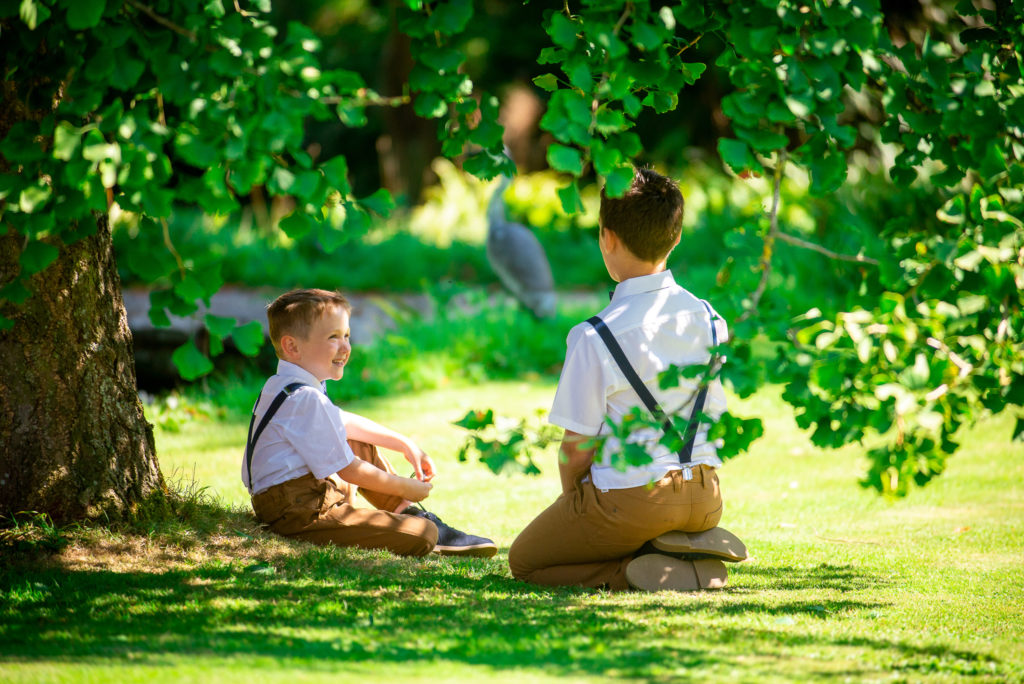 Two page boys chatting under a tree in the shade on a sunny wedding day at Pennard House in Somerset.