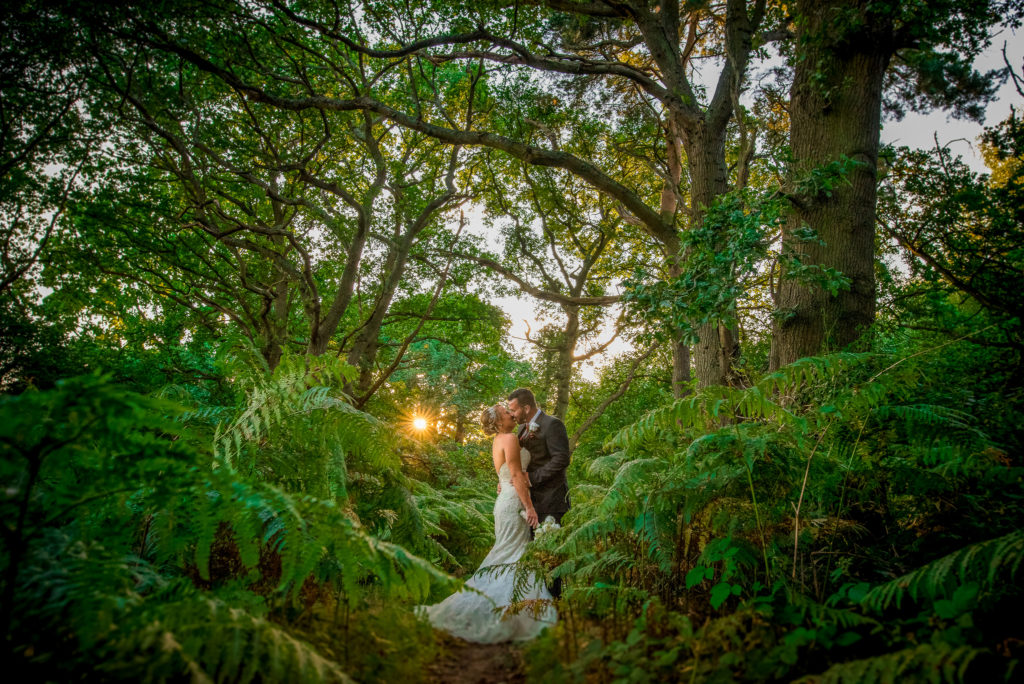 A bride and groom in the woods on their wedding day with the sun peeking through the trees.