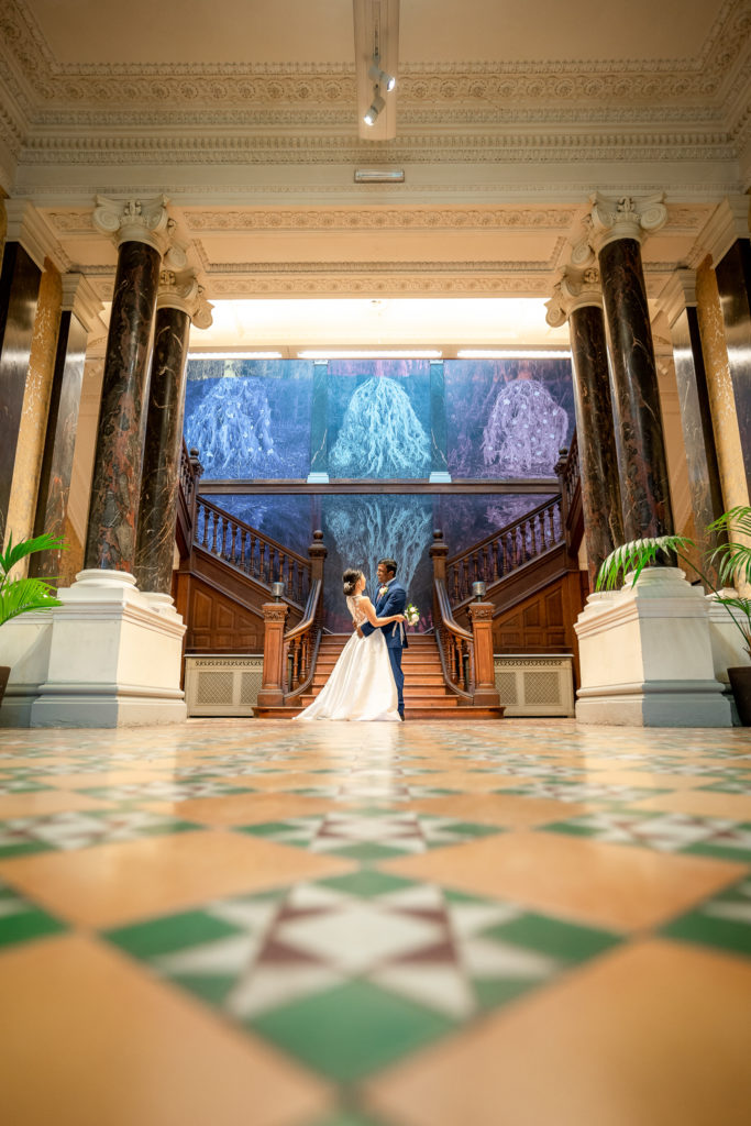 A bride and groom by the grand staircase in Hestercombe house on their wedding day.