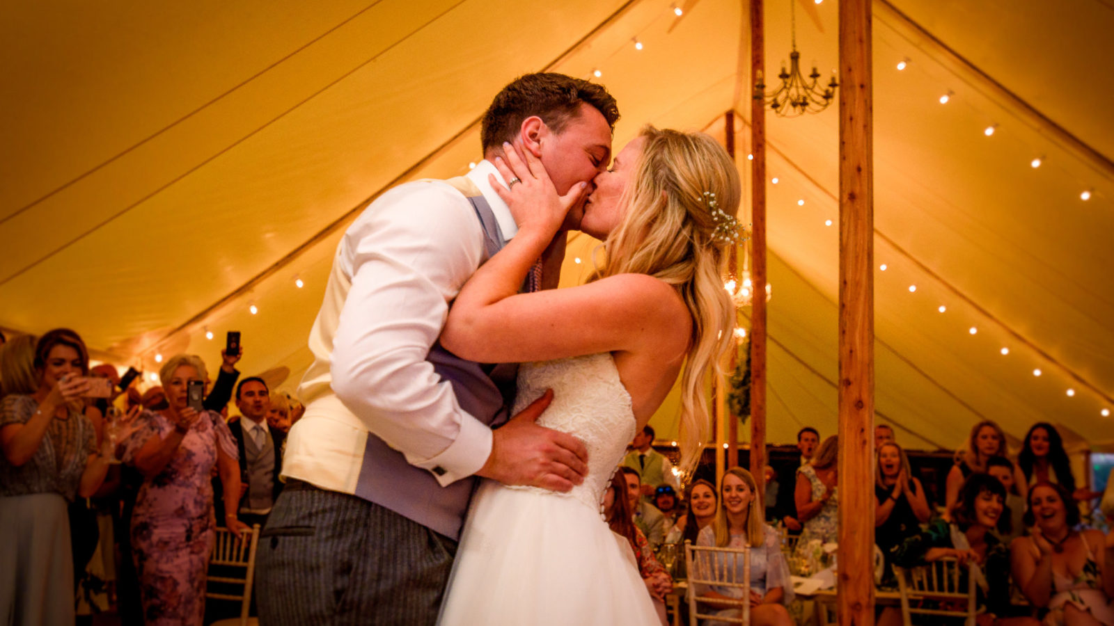 A bride and groom kissing during their first dance at their venue Old Oak Farm Wedding Venue in Somerset