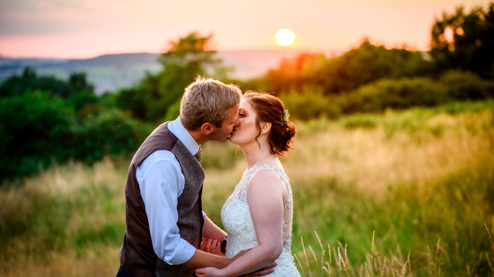 A bride and groom kissing at sunset at The River Cottage Wedding Venue in Axminster, Devon on their wedding day.