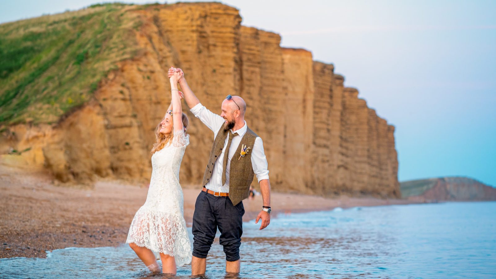 A bride and groom dancing in the sea with the cliffs of West Bay in the background in Dorset.