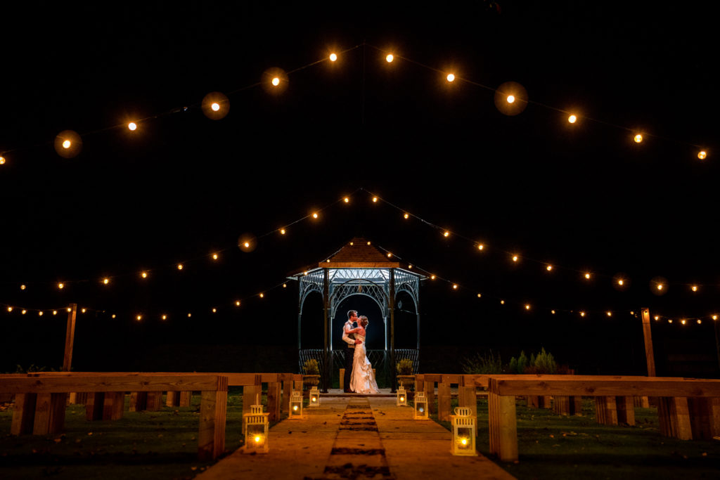 A bride and groom at night in the bandstand with festoon lights on their wedding day at The Northover Manor in Somerset.