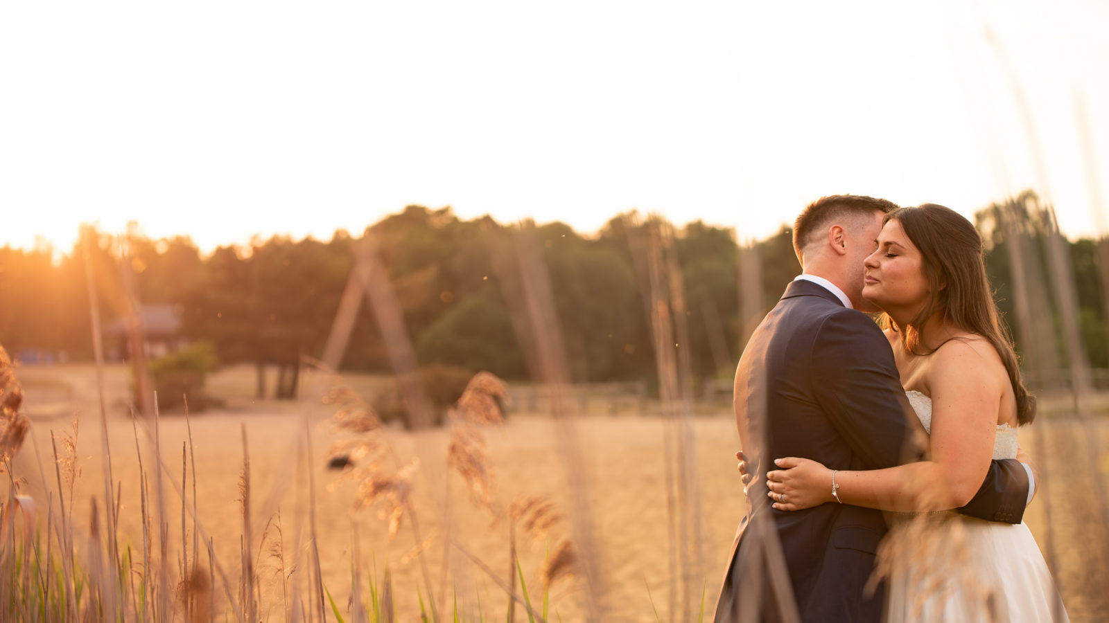 A couple hugging at sunset on their wedding day at Frensham Ponds in Hampshire.