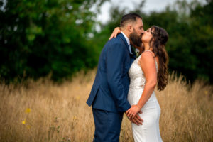 An alternative Bride and Groom kissing in the long grass at Haselbury Mill in Somerset.