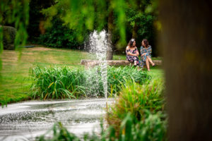 Two ladies chatting happily next to the lake outside the tithe barn at Haselbury Mill
