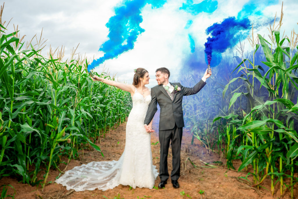 A bride and groom in a corn field on their wedding day.