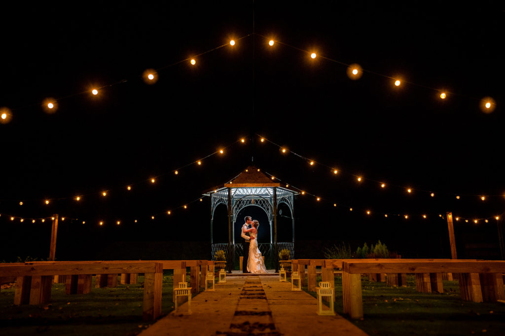 A photograph of a bride and groom under festoon lights at night at their wedding at the Northover Manor in Ilchester, Somerset.