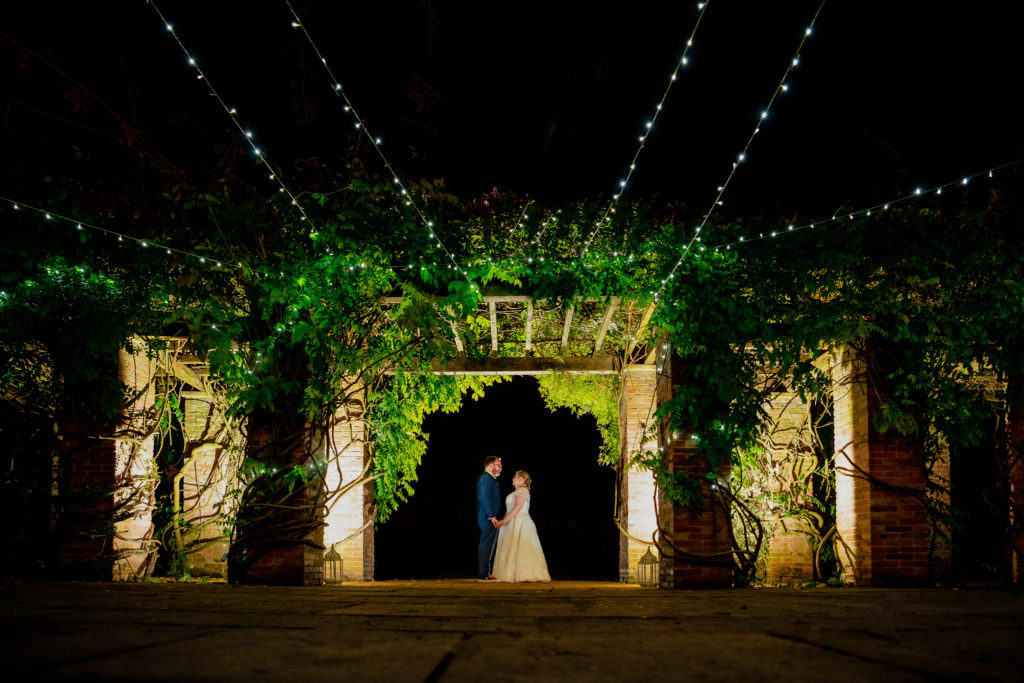 Charlton House Spa Wedding in Shepton Mallet, Somerset. A wedding night portrait of the Bride and Groom beneath fairy lights holding hand romantically.