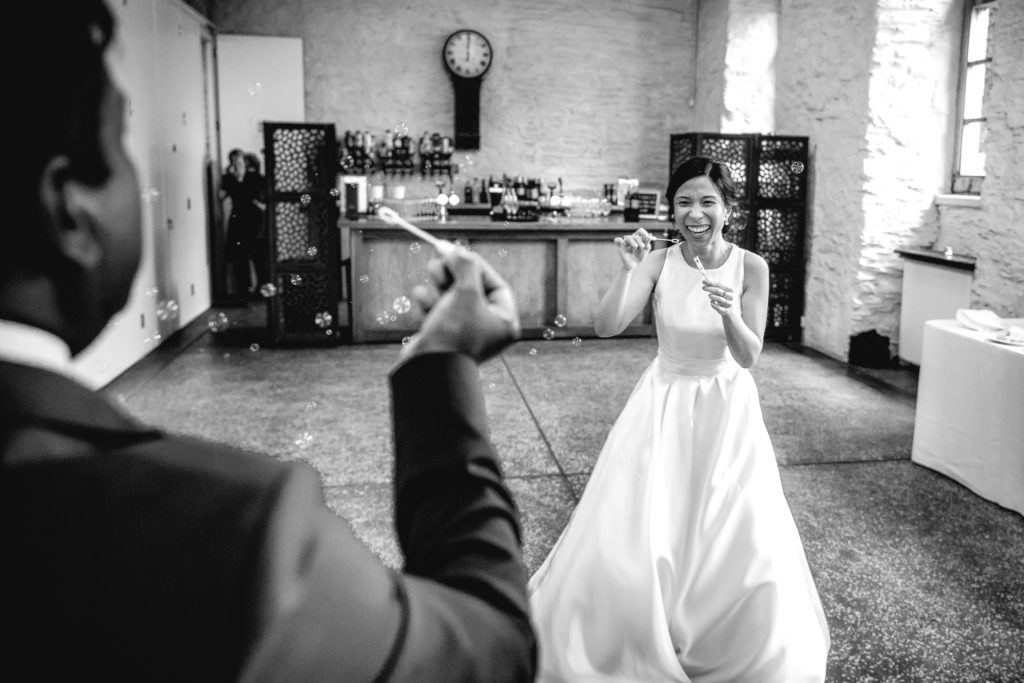 Bride and Groom having fun blowing bubbles at eachother on their wedding day at Hestercombe House and Gardens in Somerset.